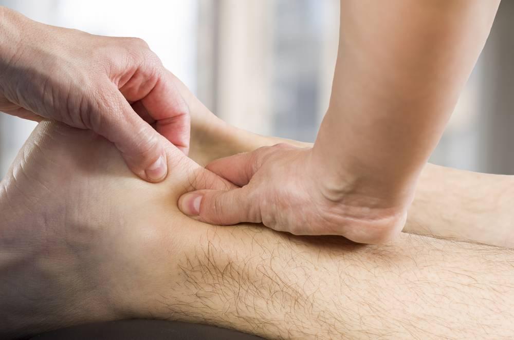 Mains d'un praticien sur l'arrière du pied d'un patient