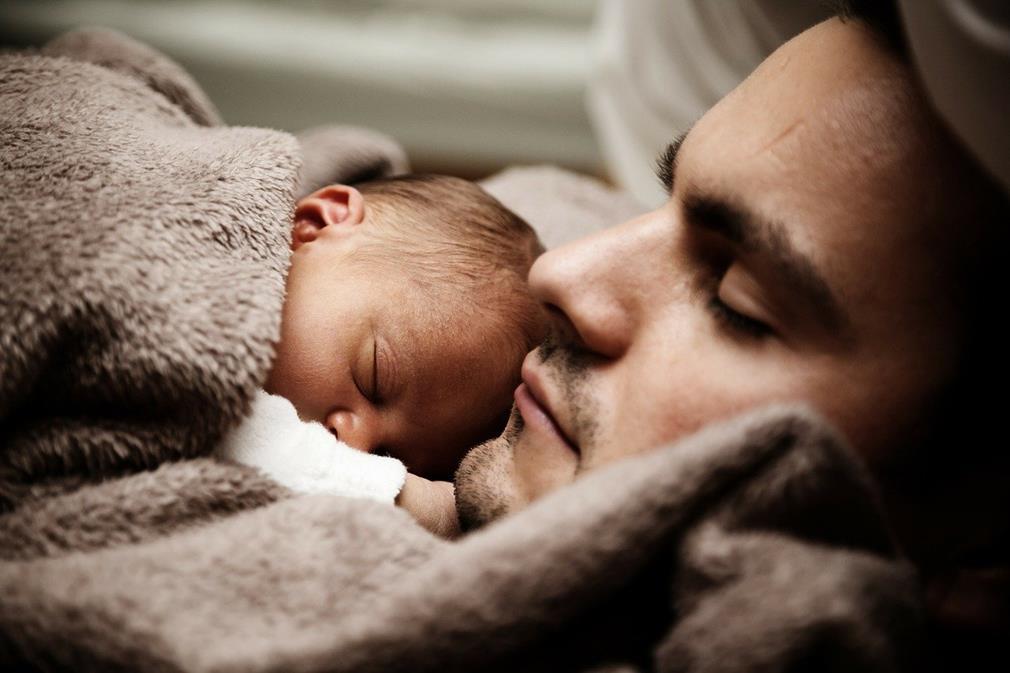 Portrait d'un homme couché, enlaçant un bébé sur son torse, tous les deux dans une couverture