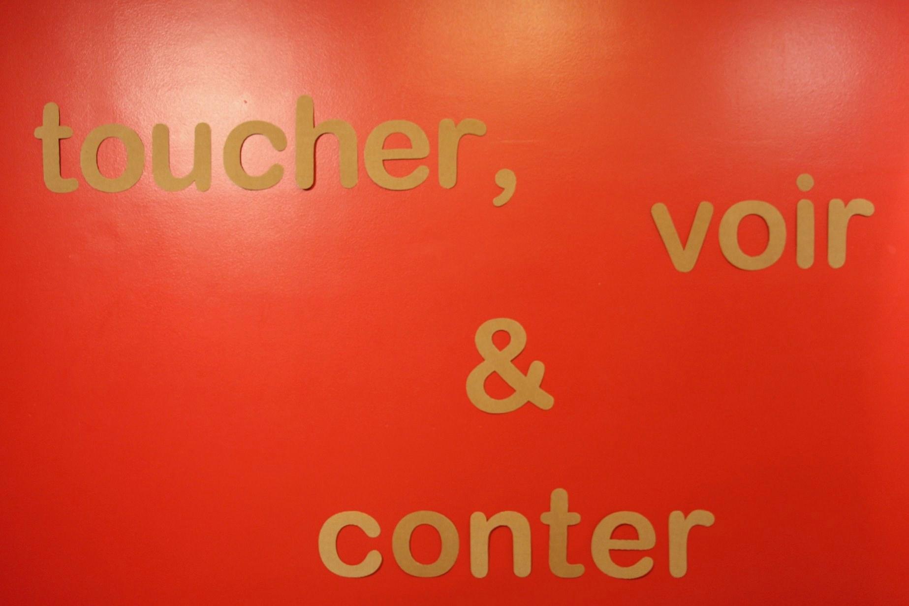 """""""toucher, voir et conter"""" écrit sur un mur"""