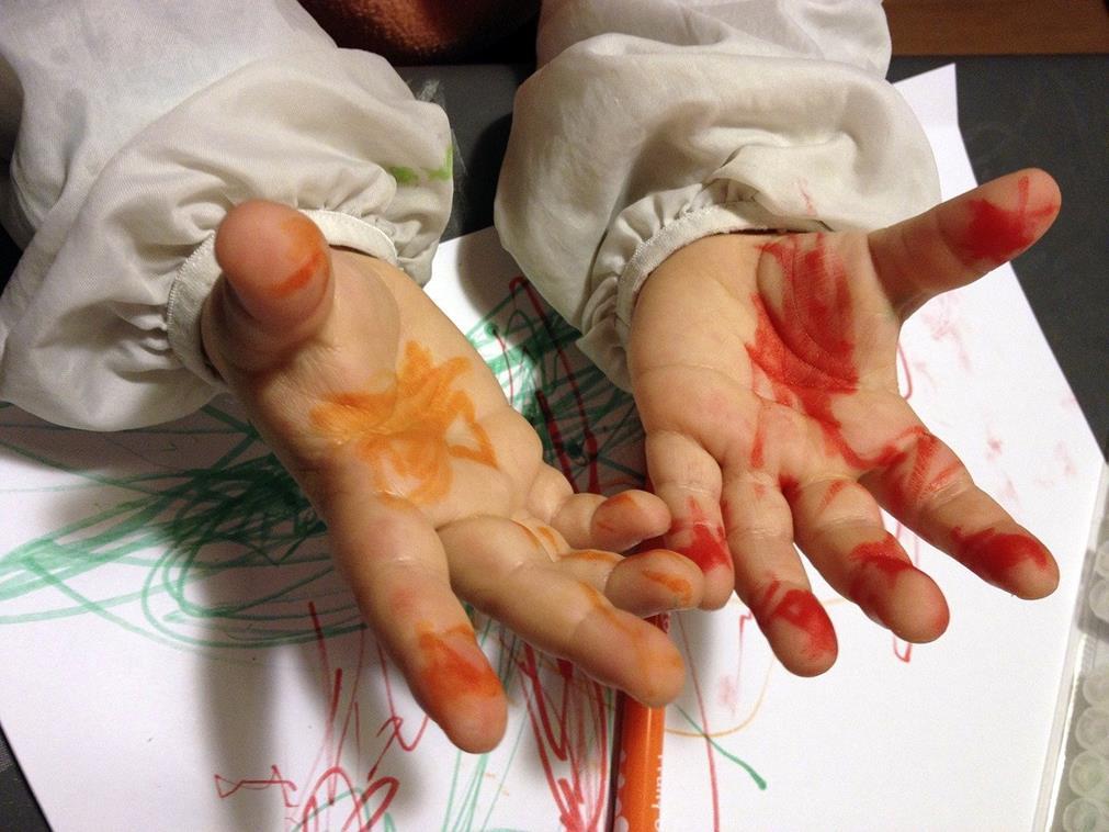 Mains d'un enfant, en cours d'art plastique, toutes barbouillées de peinture