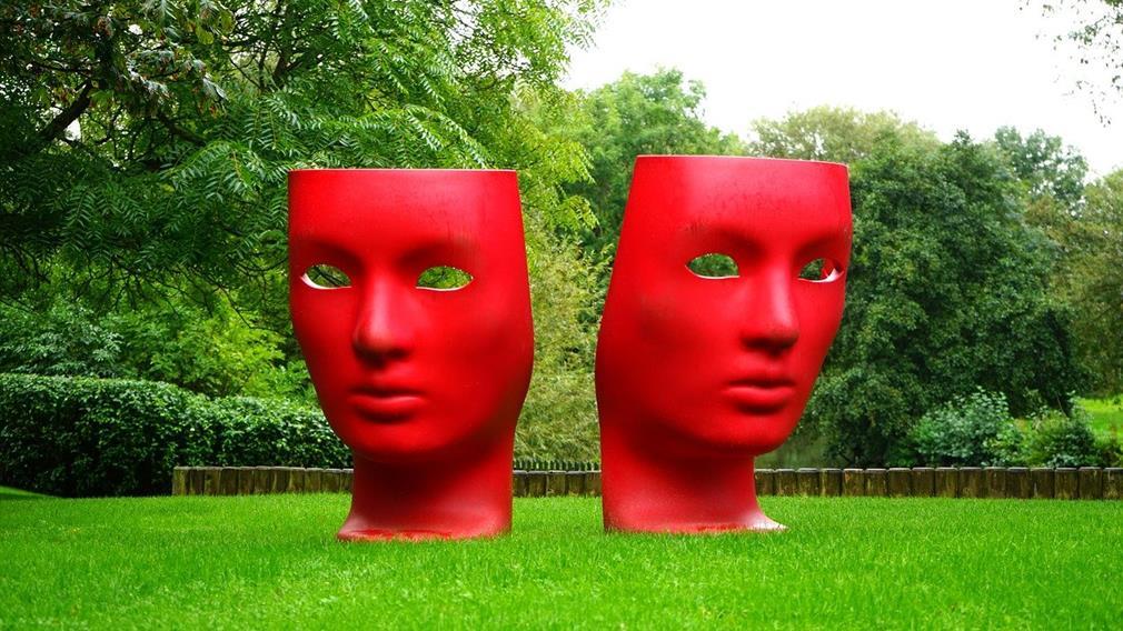Sculpture contemporaine représentant deux immenses masques comédie / tragédie dans un parc