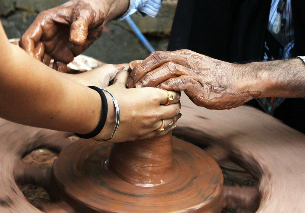 Gros plan sur deux paires de mains lors d'un apprentissage du métier de potier