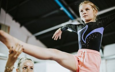 Gymnastique: les mains de l'entraîneur(e) montrent, accompagnent, écoutent et encouragent