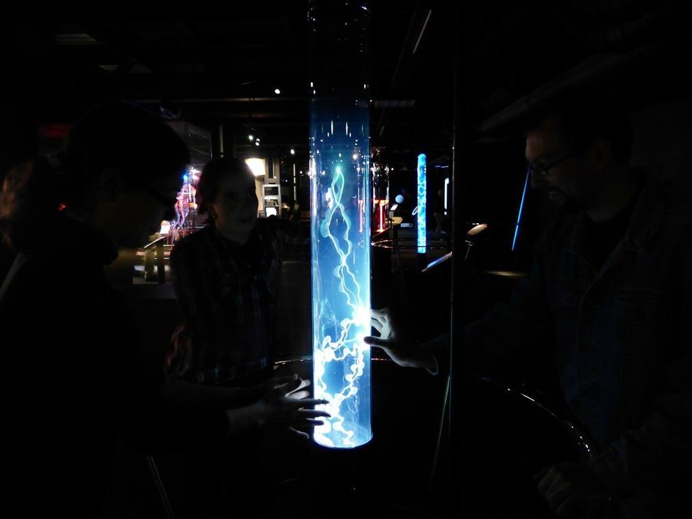 Groupe de visiteurs touchant une oeuvre lumineuse