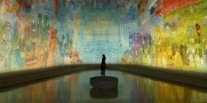 Grande salle de Musée où une peinture murale domine un visiteur