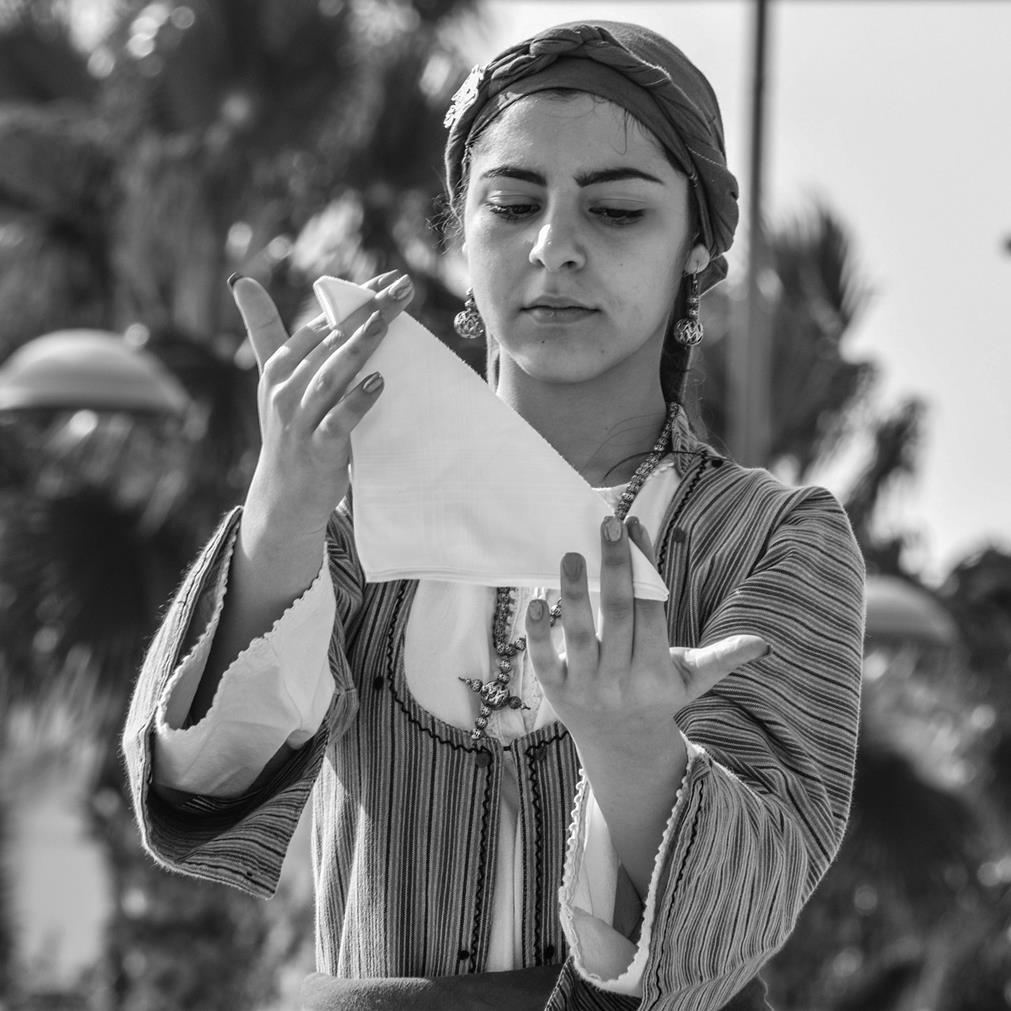 Jeune fille en costume traditionnel, maniant un tissu lors d'un numéro folklorique