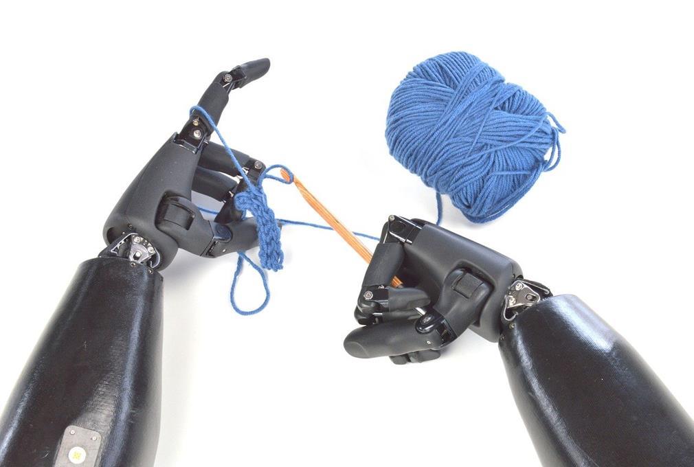 Deux mains bioniques maniant pelote de laine et aiguilles à tricoter vue de dessus