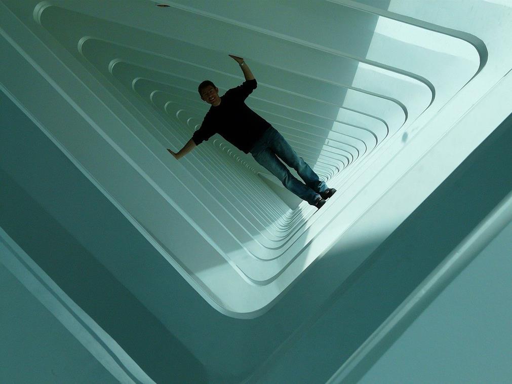 Un visiteur de musée passant à l'intérieur d'une sculpture d'art moderne (sorte de structure à couloirs)