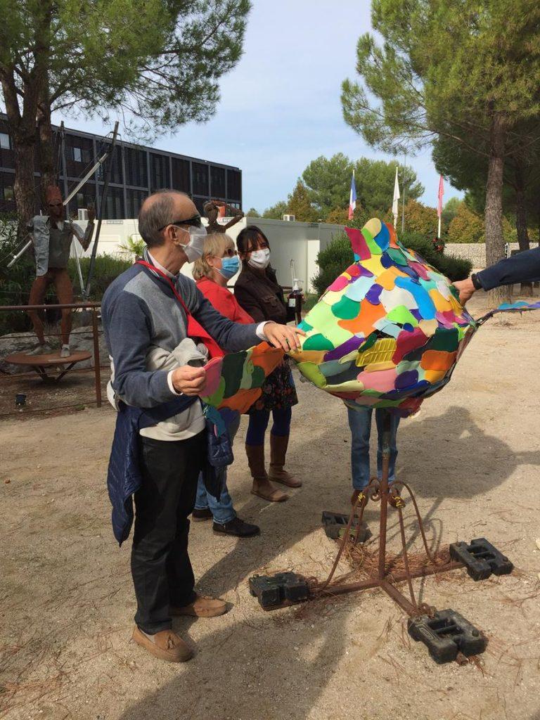 Membres d'association touchant une création artistique (sculpture de poisson) lors d'une visite tactile