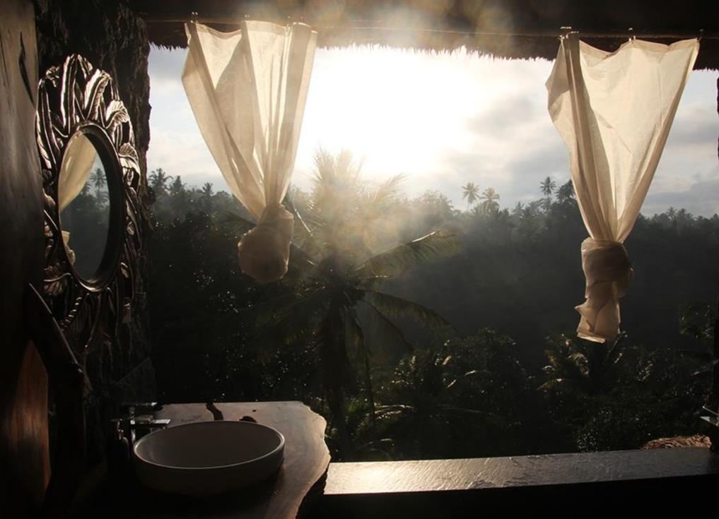 Une salle de bain, mi-ombre mi-lumière, ouverte sur un paysage tropical: sans fenêtre, un lavabo et un miroir en bois sculpté à gauche donnent sur un paysage de palmes, de fins rideaux laissant filtrer des rayons de lumière