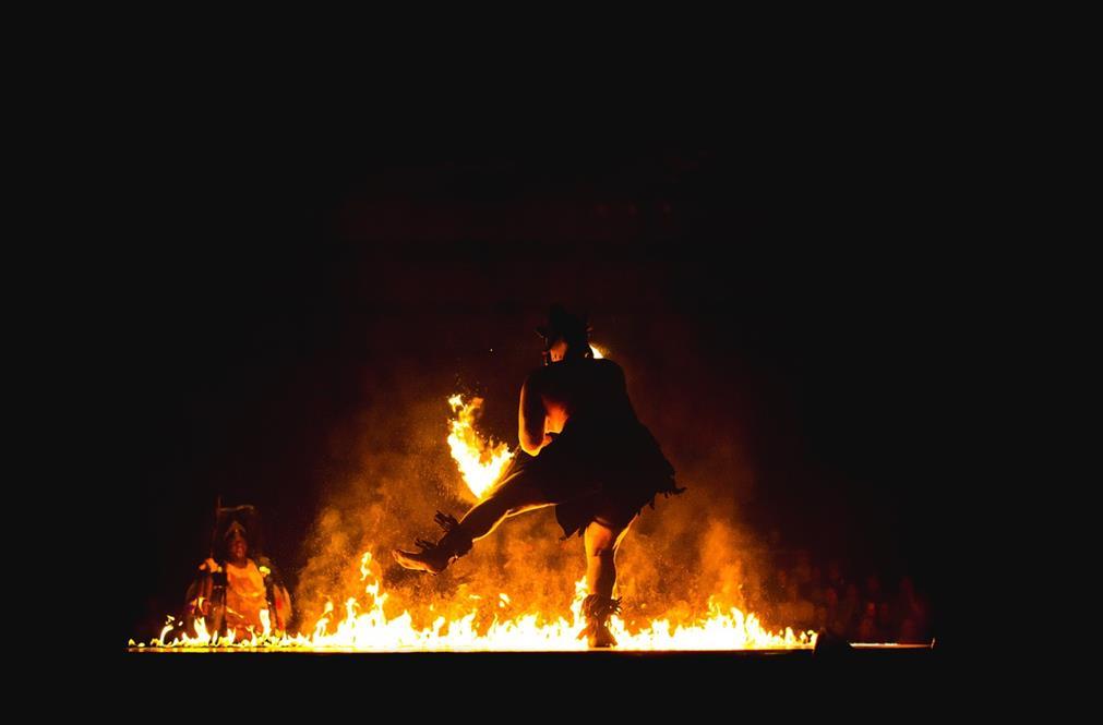 Un rituel tribal: en pleine nuit, de dos, un homme en costume traditionnel polynésien effectue un rituel autour d'un feu, en maniant les flammes. On distingue d'autres participants en arrière plan, dans la pénombre
