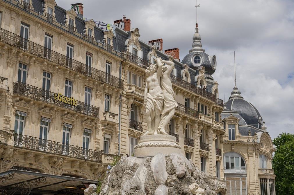 La statue des trois grâce, Place de la Comédie à Montpellier. Trois femmes, dos à dos, partiellement nues et debout trônent en haut d'une fontaine représentant des rochers. En fond, on distingue la coupole d'un cinéma ainsi que des bâtiments d'époque