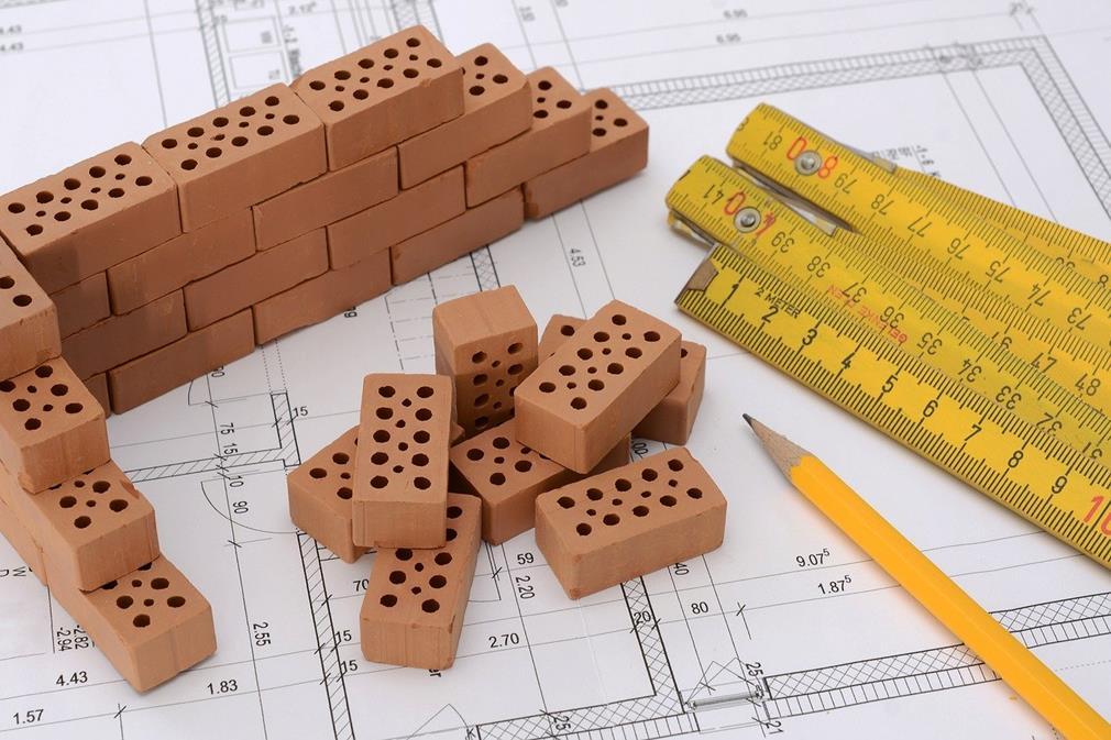 Vue d'une table de travail d'un architecte: des petites briques de construction de maquettes sont empilées pour commencer à monter un mur, un crayon et des règles sont posés sur un plan