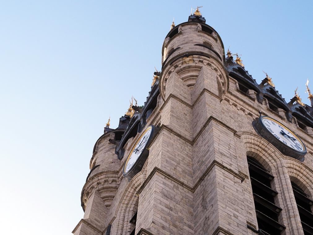 En contre-plongée, le beffroi de Douai: aux  angles de ce bâtiment carré, des tourelles pointues ; sur chaque face du bâtiment, un cadran d'horloge doré