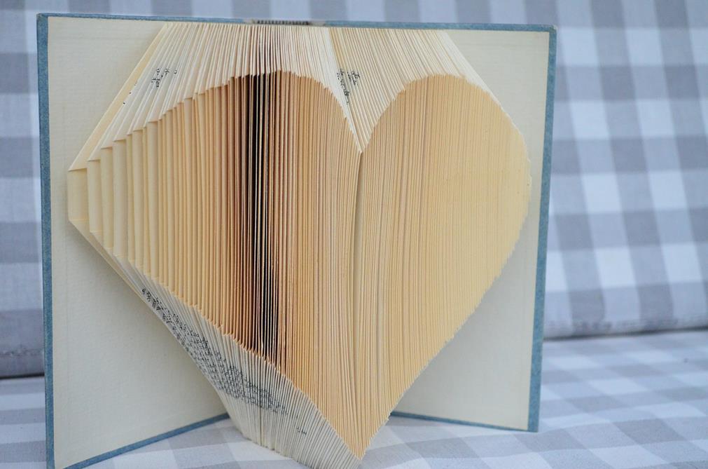 Une oeuvre d'art: un livre posé droit, ouvert, de face, dont les pages sont pliées en origami pour créer les contours d'un coeur sortant du support