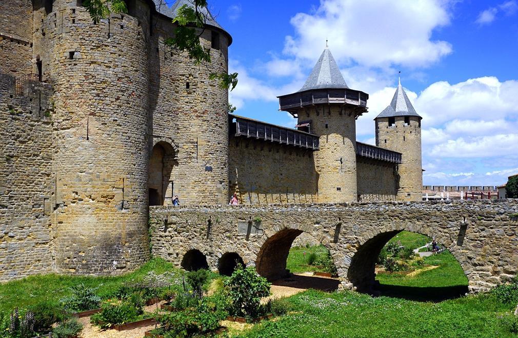 L'une des entrées de la cité de Carcassonne : un pont enjambe les douves en herbes et jardins de simples, les remparts avec tourelles se profilent tout le long d'un côté