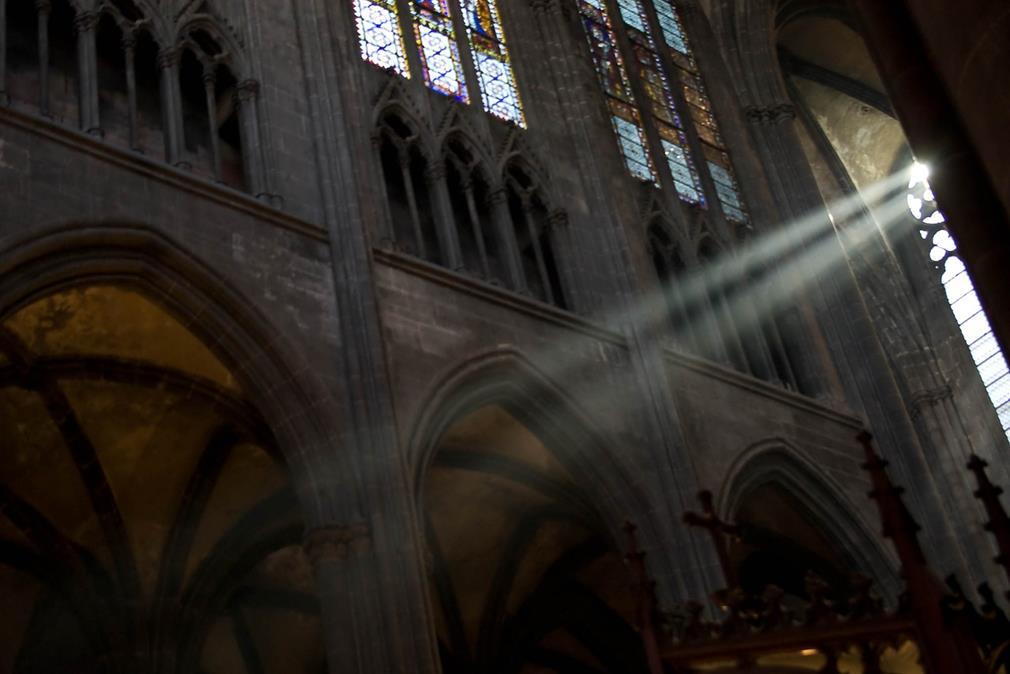 Intérieur de la cathédrale de Clermont-Ferrand: la lumière filtre à travers les vitraux d'un côté du bâtiment, au-dessus d'une enfilade d'arches