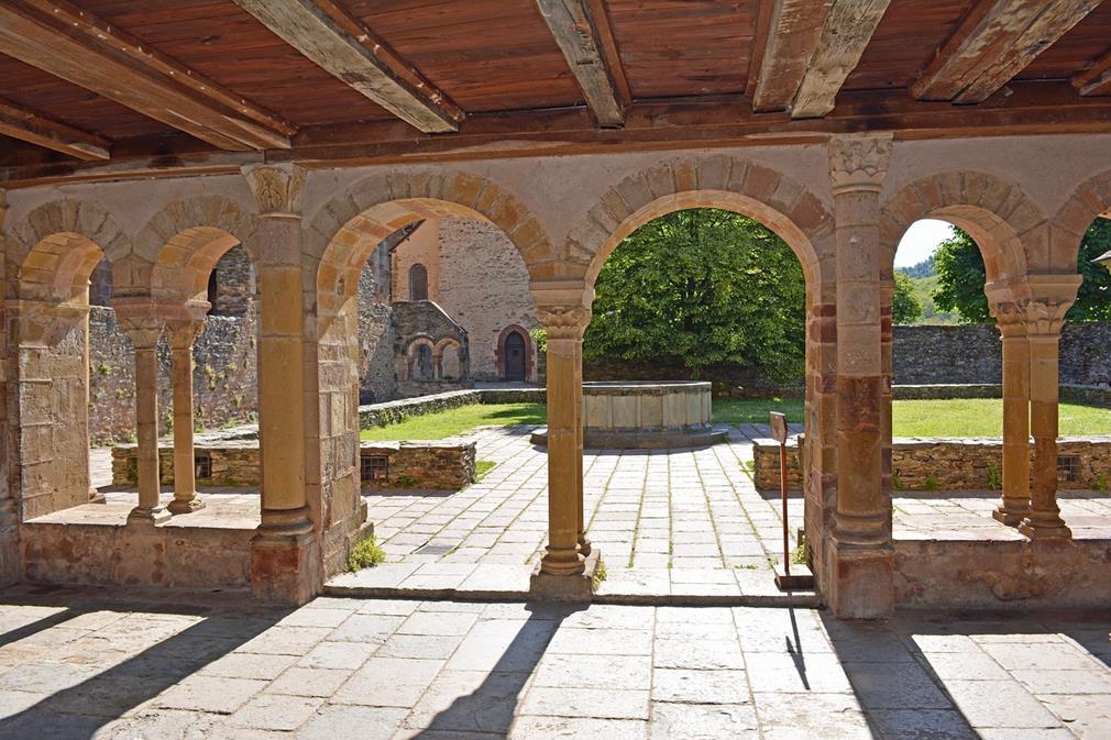 Cloître de l'Abbaye de Conques: depuis la coursive, les arches encadrent le centre arboré de la cour, on distingue un jeu d'ombres et de lumière entre les piliers