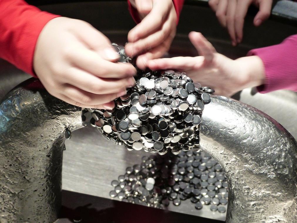 En gros plan, des mains d'enfants touchent et manipulent les éléments d'une structure magnétique, composée de petits aimants argent, dans une cuve