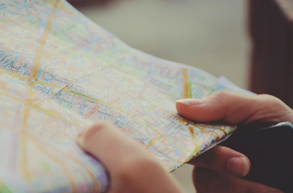 En gros plan, des doigts tiennent et parcours une carte routière