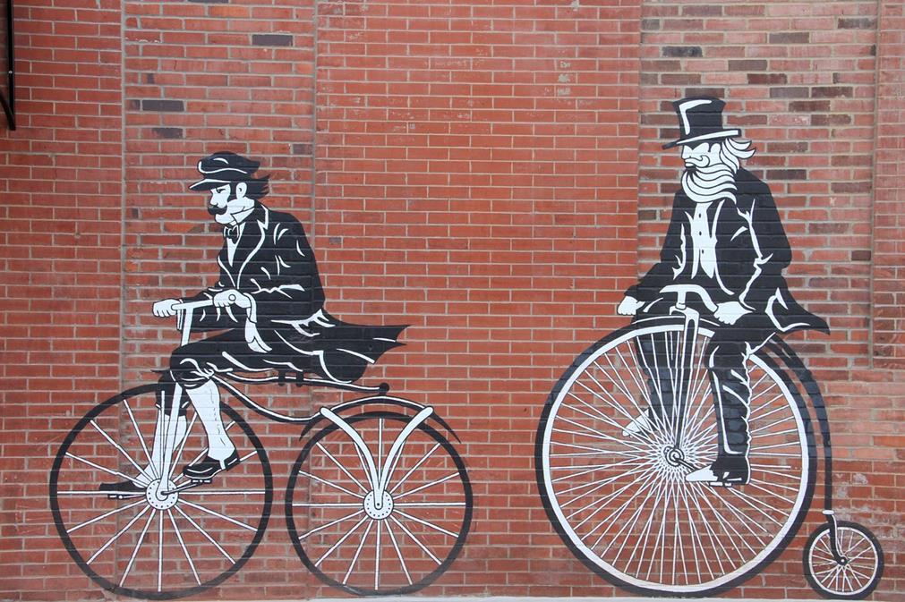 Art mural: sur un mur de briques rouges, un collage représente deux hommes en queue de pie, haut-de-forme, moustaches et barbe, se suivant chacun sur une ancienne forme de vélo: le premier sur l'un des premiers modèles de bicyclette, le second sur un monocycle
