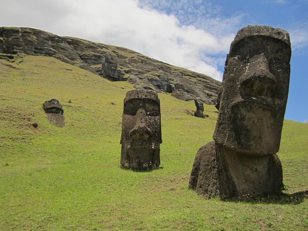 Les têtes de l'Île de Pâques : sur une colline herbeuse, les têtes en pierre sortent à mi-buste, certaines droites, d'autres penchées, tout le long du mont