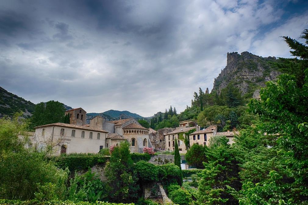En contre-plongée, Saint-Guilhem le Désert. Le village médiéval s'élève au-dessus des gorges recouvertes de verdures, sur un ciel très présent. En hauteur, des apiques encadrent les habitations