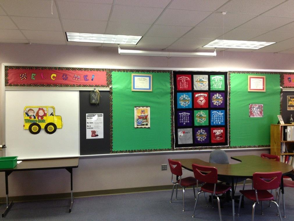 Une salle de classe : le tableau est recouvert d'images composées de divers éléments (lettres en feutrines qui forment le mot welcome, petits dessins encadrés comme des tableaux, voitures en semi-relief)