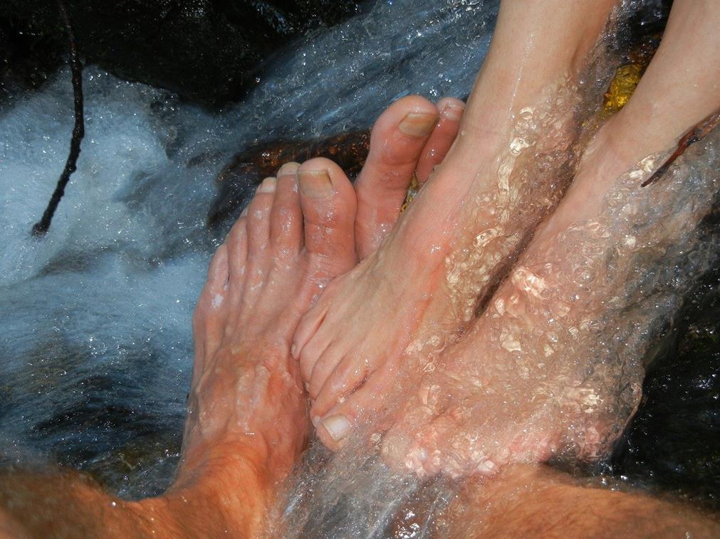 Au coeur d'un ruisseau de montagne, gros plan sur deux paires de pieds nus qui reposent l'une sur l'autre dans une caresse mutuelle. On distingue des rochers tandis que l'eau s'écoule sur les pieds