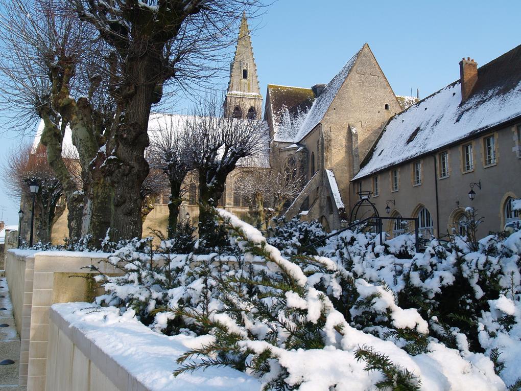 """Vue de l'Abbaye de Ferrières sous la neige : la ville a obtenu le label """"Petites cités de caractère"""" : au premier plan, des haies parsemées de neige bordent le corps de l'abbatiale, en vue de trois-quarts. Au fond, le clocher dépasse, au milieu d'arbres nus. On distingue différents styles de vitraux (abbaye bénédictine fondée à l'époque mérovingienne)."""