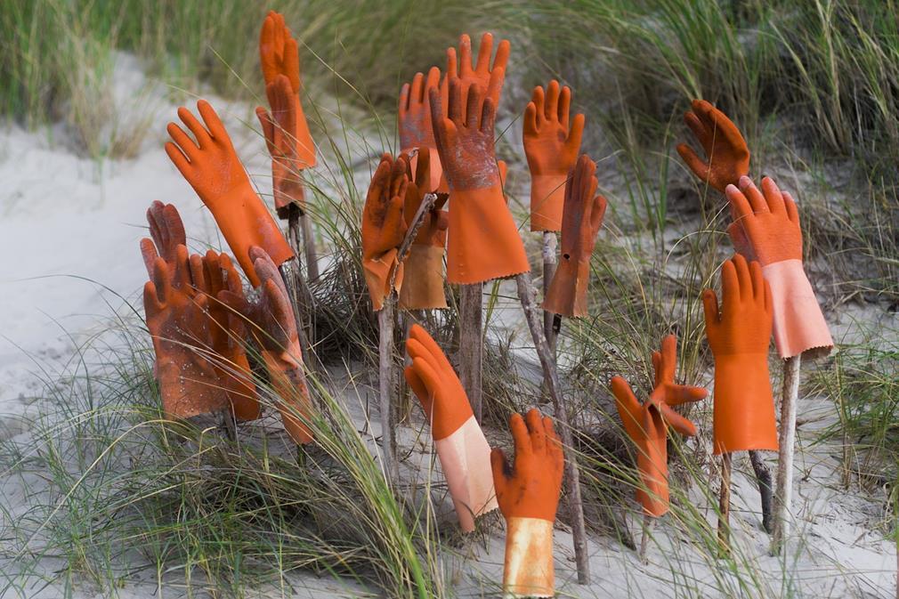 Approche artistique contemporaine pour cette photographie: sur une dune, au milieu du sable et des herbes hautes, une quinzaine de gants de cuisine et/ou de travail, vides, sont plantés comme abandonnés sur des bâtons, à la verticale, en un regroupement