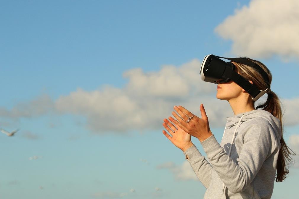 De profil, sur un fond de ciel bleu parsemé de nuage, une femme porte un casque de réalité virtuelle. Elle tient se mains relevées devant elle, paumes vers le haut, comme pour sentir les informations que lui fait vivre le casque.