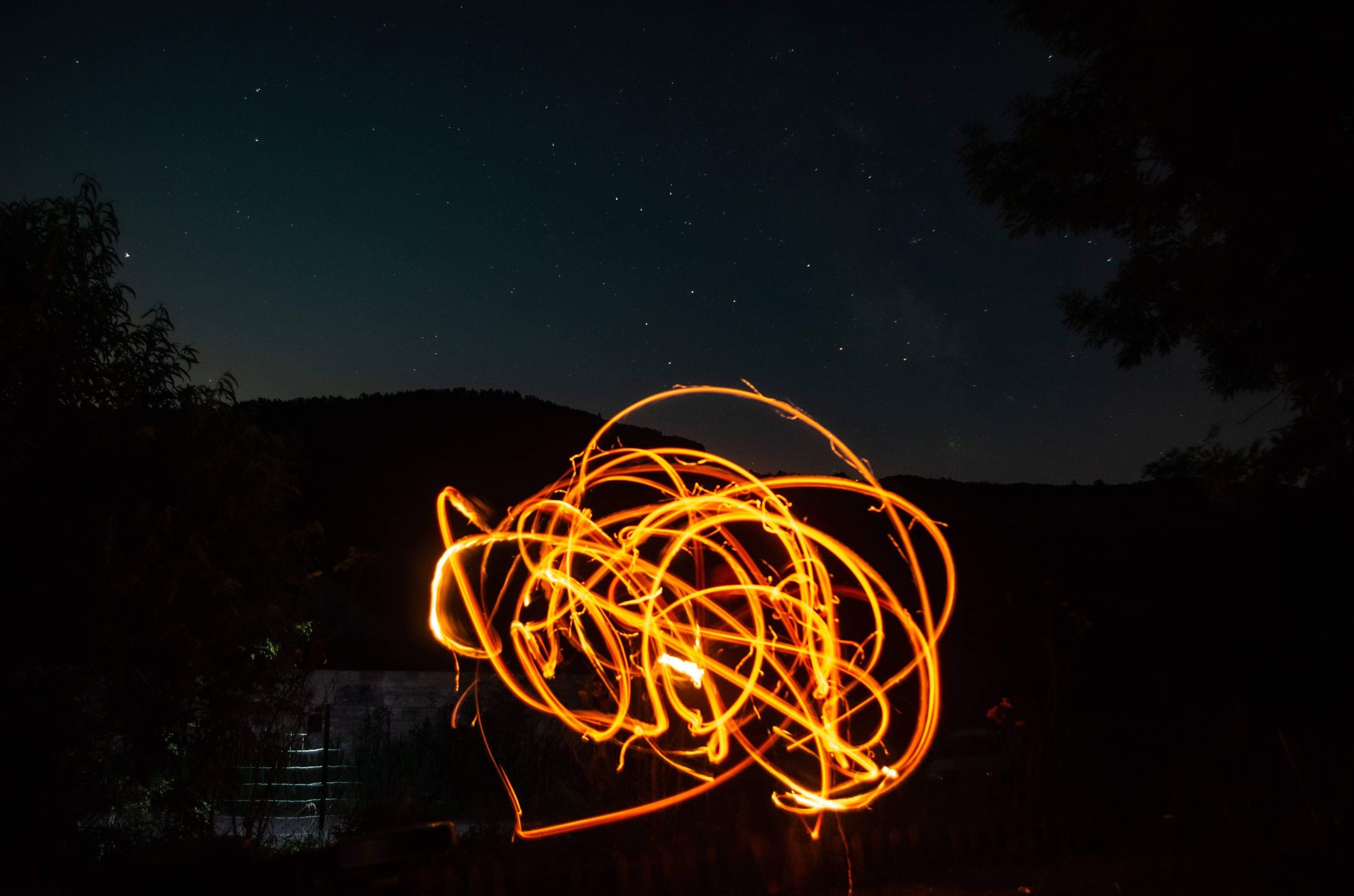 Composition artistique par technique de stop motion: sur un fond de ciel étoilé de montagne, des prises successives d'images accolées forment une composition abstraite rendue  possible par le mouvement d'un bâton enflammé  dans l'air. L'effet est un tourbillon de feu, qui semble voler dans ce ciel.
