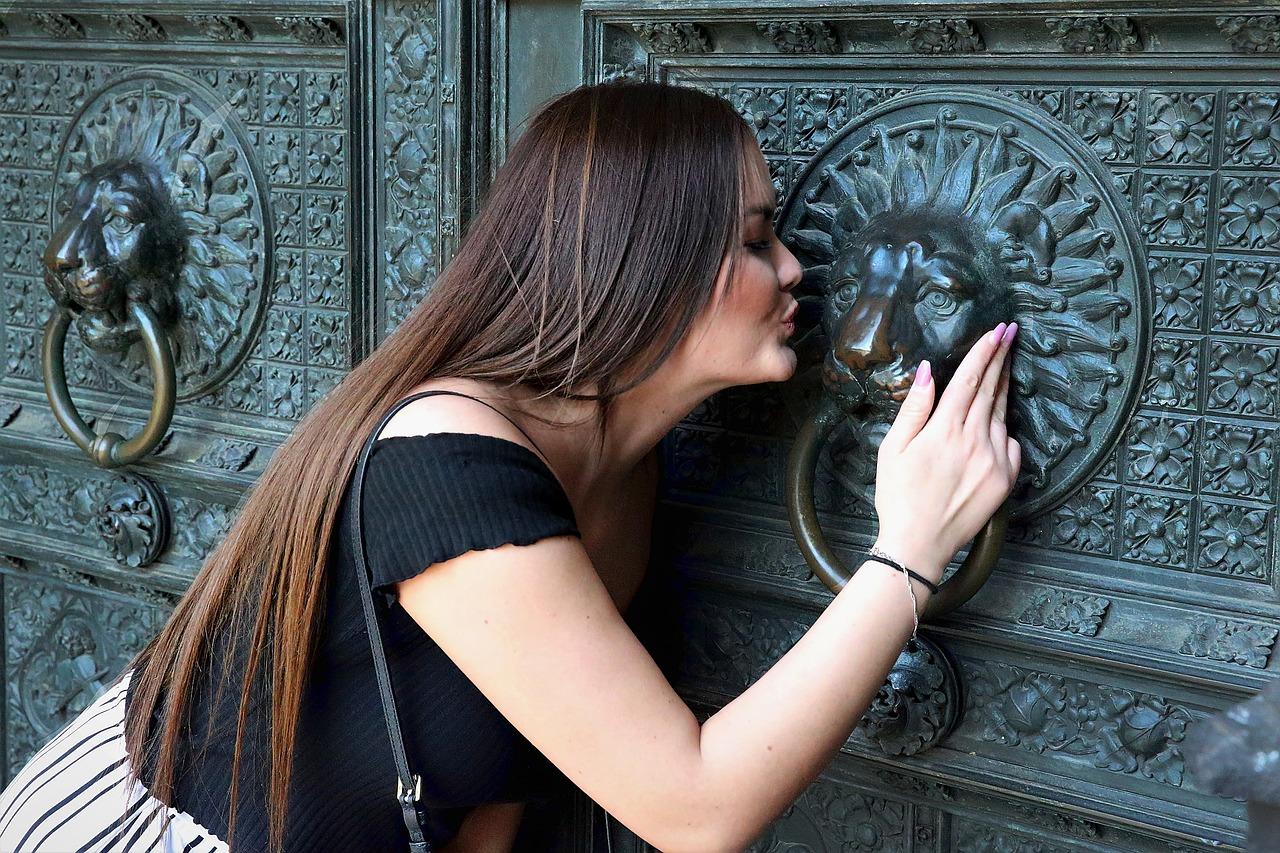 Une femme de profil, appuyant son buste contre une vieille porte d'entrée en fer forgé, se penche pour embrasser l'énorme heurtoir en tête de lion, l'enlaçant de sa main droite